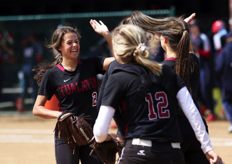 TIMES PHOTO: DAN BROOD - Tualatin sophomore Tia Ridings (left) is all smiles as she's being congratulated by her teammates during Saturday's game.