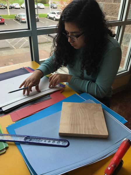 PHOTO CONTRIBUTED BY KATIE SULLIVAN - Sam Reitiz, a senior, cuts up large white letters out of paper for her project. She describes how she and her fellow artists have become like a tight-knit family.