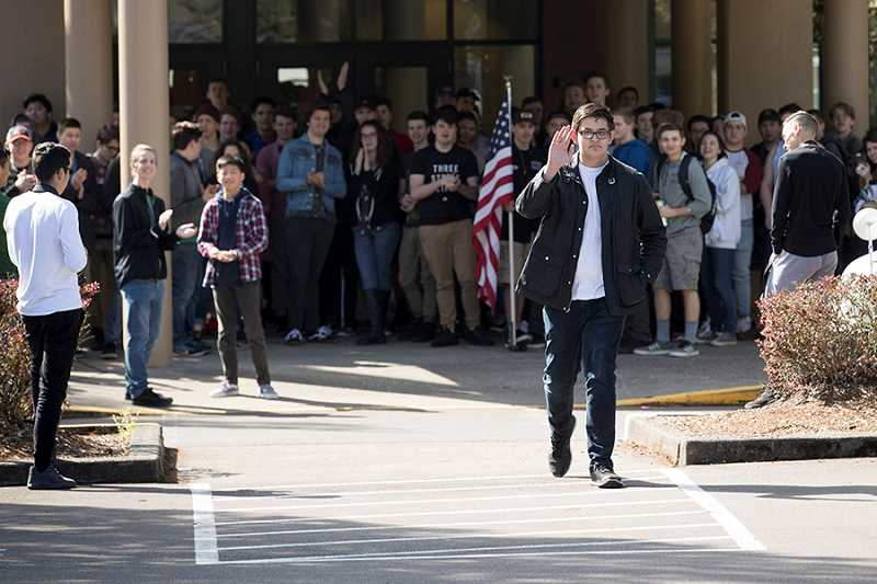 TIMES PHOTO: JAIME VALDEZ - Tigard High School sophomore Bonifacio Yuzon walks toward area television and print media reporters to chat after holding a rally in front of the school in support of Second Amendment rights.