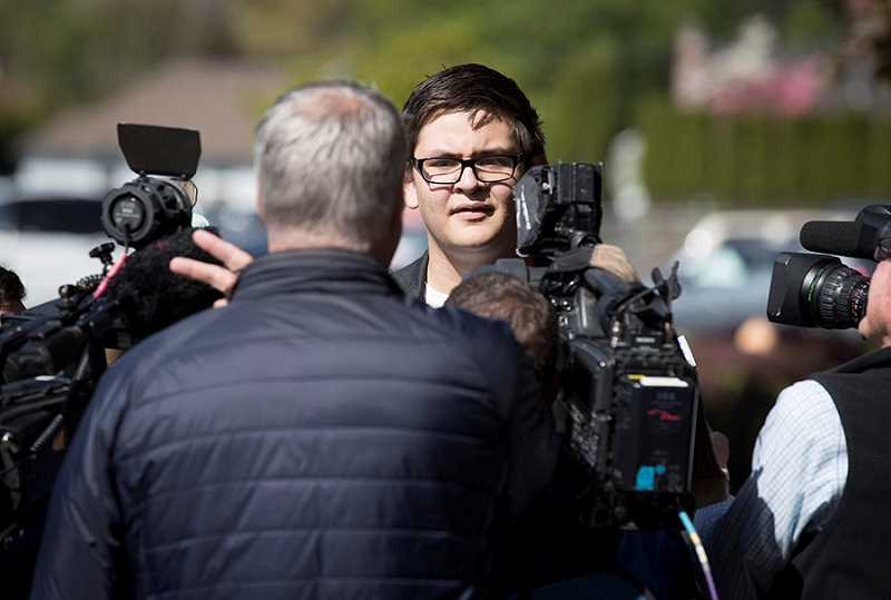 TIMES PHOTO: JAIME VALDEZ - Bonifacio Yuzon talks with area television and print reporters along Durham Road after holding a rally in support of the Second Amendment.