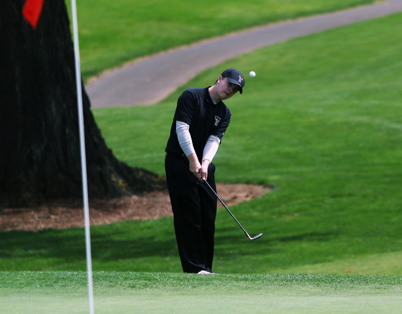 TIMES PHOTO: DAN BROOD - Tualatin High School sophomore Bryce Hatcher chips onto the green during play Monday at the Three Rivers League district tournament.