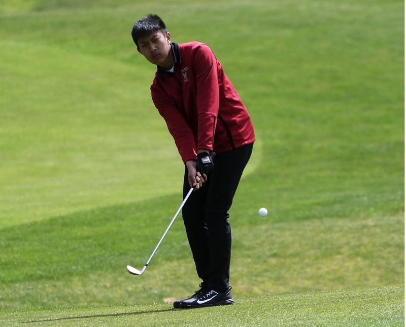 TIMES PHOTO: DAN BROOD - Tualatin's Elijah Lai chips onto the green during play Monday at the Three Rivers League district tournament.
