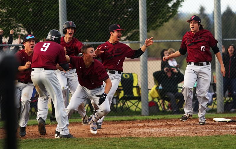 TIMES PHOTO: DAN BROOD - The Tualatin High School baseball team celebrates at home plate after senior Ryan Webb (9) scored the game-winning run in Tuesdays contest with Tigard.