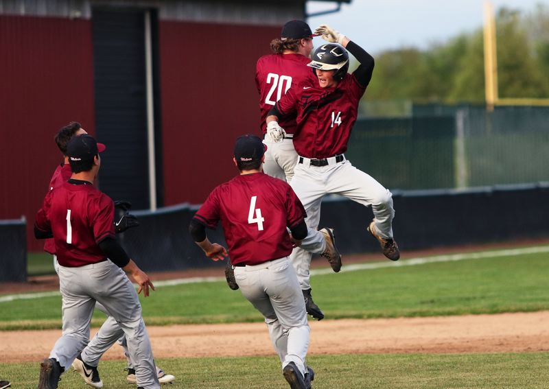 TIMES PHOTO: DAN BROOD - Tualatin High School sophomore Blake Jackson (14) celebrates with his teammates after driving in the game-winning run in Tuesdays contest with Tigard.
