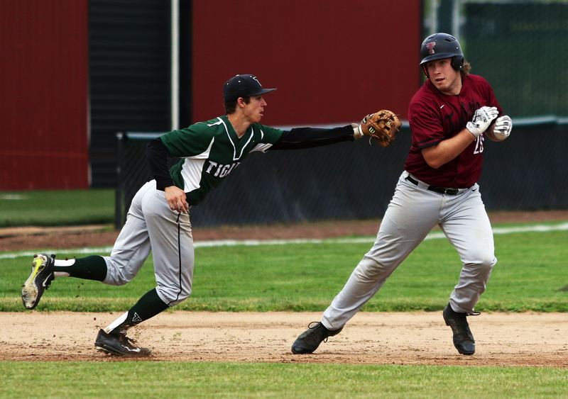 TIMES PHOTO: DAN BROOD - Tigard High School senior shortstop Michael Quintana (left) goes to tag Tualatin junior Gavin Moore during a rundown in Tuesdays game.