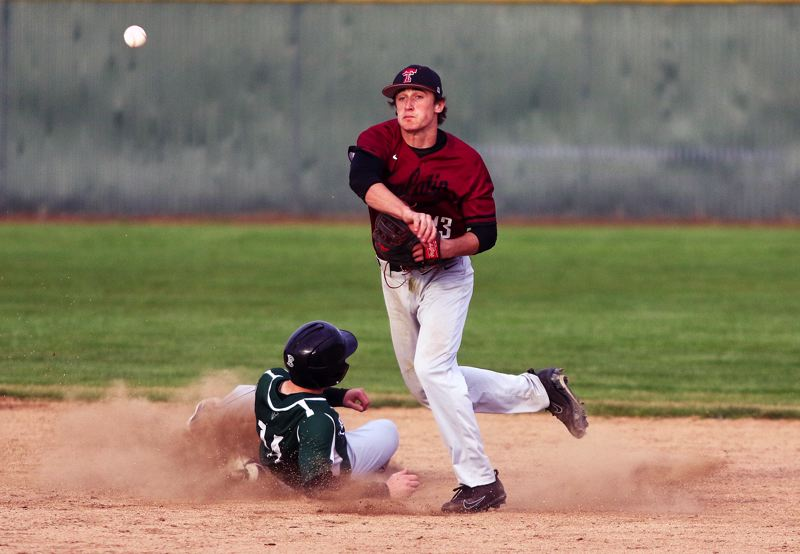 TIMES PHOTO: DAN BROOD - Tualatin senior second baseman Colby Jackson makes a throw to first base, as Tigard sophomore Fletcher Ahl slides to the bag, to complete a double play.