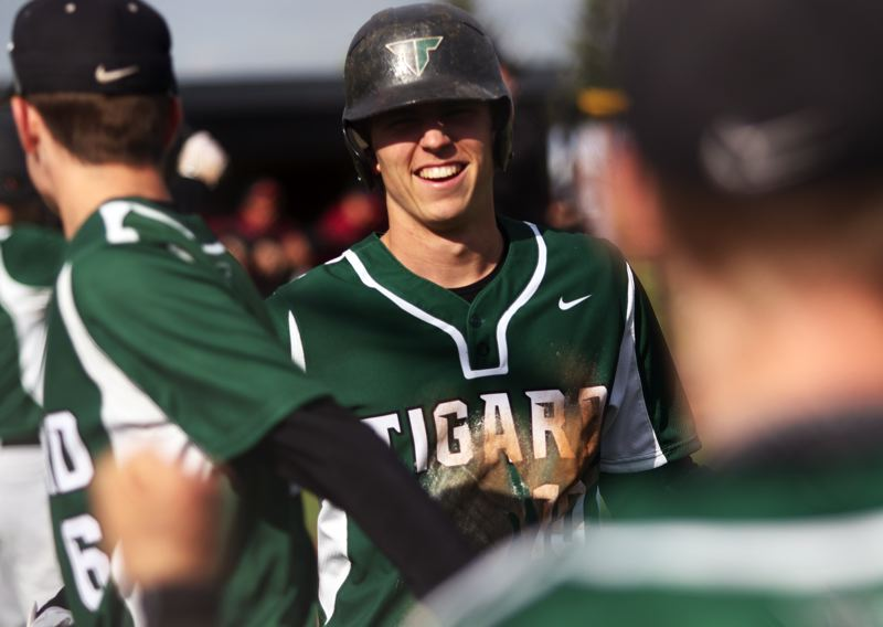 TIMES PHOTO: DAN BROODTHE  - Tigard High School senior Nick Heinke is all smiles after scoring the first run of the game in Tuesdays TRL contest at Tualatin.
