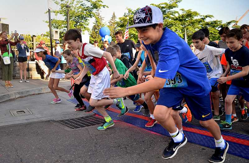 REVIEW PHOTO: VERN UYETAKE - Children bolt from the starting line at last year's Kids Dash, a two-block scramble that finishes under a big balloon arch. The Lake Run also includes 10K and 5K races.