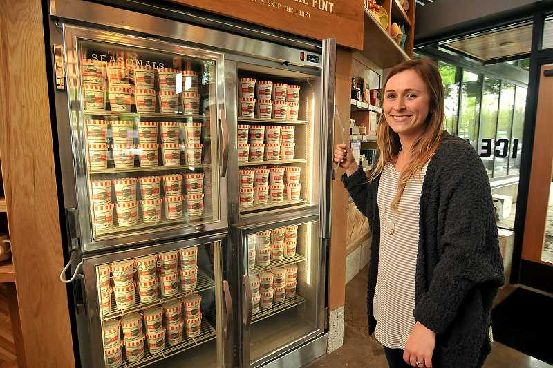 REVIEW PHOTO: VERN UYETAKE - Salt & Straw Marketing Manager Colleen Schwab stands next to a refrigerator case full ice cream in the company's new Lake Oswego shop, which officially opens on Friday.
