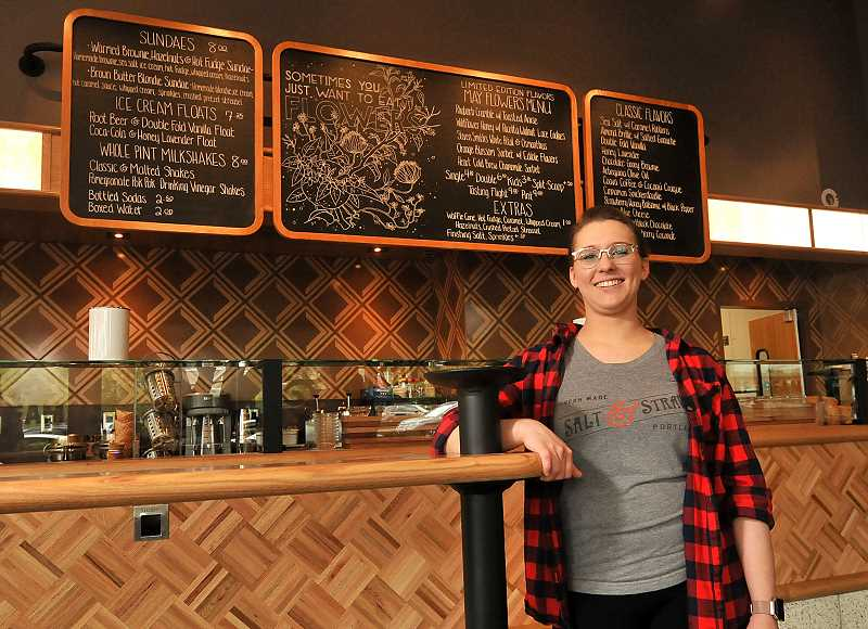 REVIEW PHOTO: VERN UYETAKE - Salt & Straw Marketing Coordinator Amber Hartman stands in front of menu board in the company's new Lake Oswego Shop, which will feature a 'May Flowers' seasonal menu when it opens Friday.