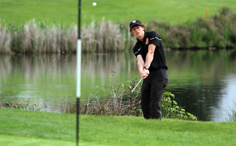 SPOTLIGHT PHOTO: MILES VANCE - Scappoose senior Jake Gray chips onto the green at Quail Valley Golf Course in Banks during Monday's Cowapa League tournament.
