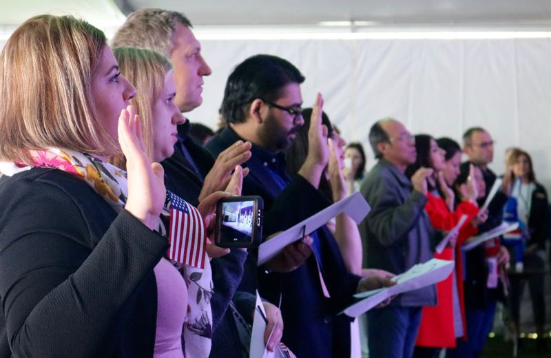 TRIBUNE PHOTO: ZANE SPARLING - New citizens swear the Oath of Allegiance during a naturalization ceremony on Friday, May 4, at Tom McCall Waterfront Park in downtown Portland.