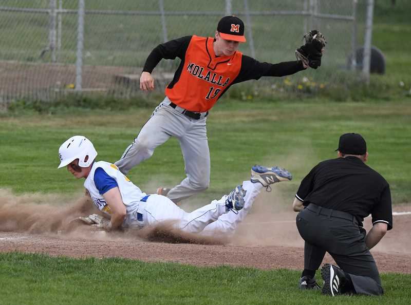 LON AUSTIN/CENTRAL OREGONIAN - Crook County's Brody Connell slides safely into third. The Cowboys came from behind to defeat the Indians 17-8 in Tri-Valley Conference action Friday afternoon in Prineville.