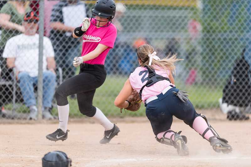 STAFF PHOTO: CHRISTOPHER OERTELL - Scappoose's Taylor Johnson narrowly avoids the tag of Banks catcher Hannah McCourt during the Braves' game against the Indians May, 4, at Banks High School.
