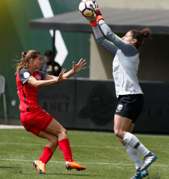 TRIBUNE PHOTO: JONATHAN HOUSE - Seattle Reign goalkeeper Michelle Betos gets to a ball before Tobin Heath of the Portland Thorns. Seattle prevailed, 3-2, on Saturday afternoon at Providence Park.