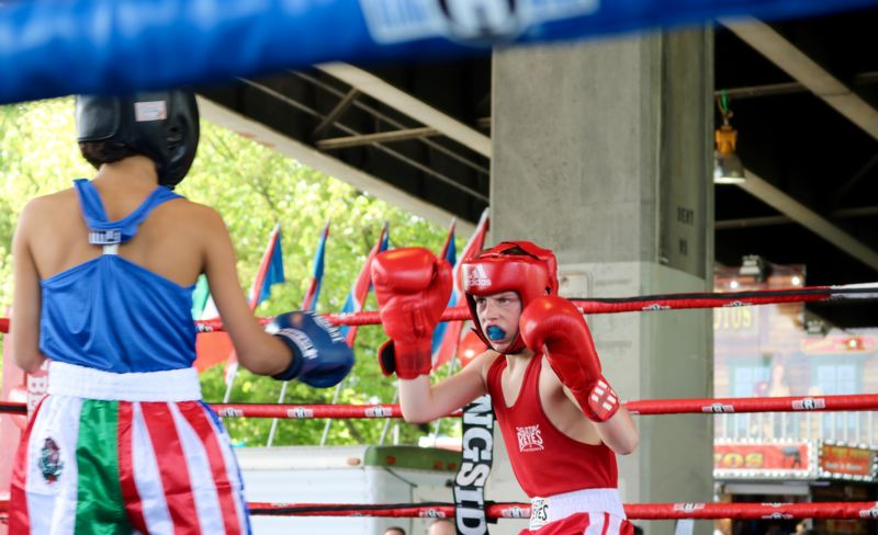 TRIBUNE PHOTO: ZANE SPARLING - Matthew Charlton (center) eyes opponent Roberto Sanchez of Idaho during a boxing match for 90-pound 13-year-olds during Cinco de Mayo on Saturday, May 5 in Portland.