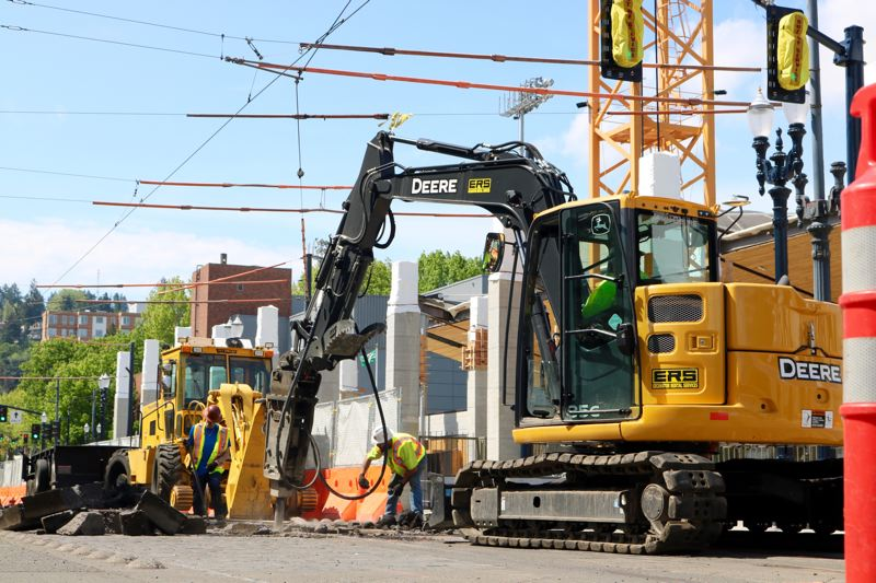 TRIBUNE PHOTO: ZANE SPARLING - Workers tear up MAX light-rail tracks near Providence Park on Sunday, May 6.