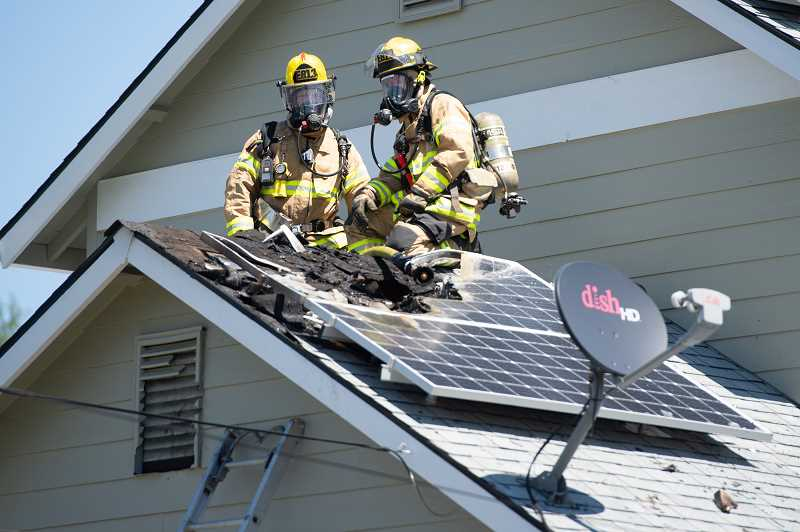 STAFF PHOTO: CHRISTOPHER OERTELL - Firefighters from Cornelius Engine 813 sit at the ready on a garage roof in case fire reignites on a house fire on S 26th Ave. in Cornelius, Ore., on Monday, May 7, 2018.
