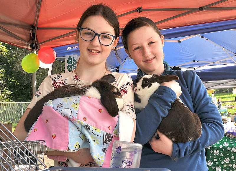 OUTLOOK PHOTO: VERN UYETAKE - Twin sisters Lizzie, left, and Annie Loveland will show their rabbits Bun-Bun and Brendan at the Multnomah County Fair.