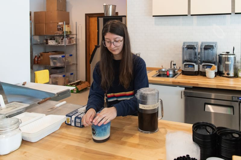 STAFF PHOTO: CHRISTOPHER OERTELL - Kafe employee Alecia Boehlke puts the lid on an anchan boba tea, one of many drinks served at the new Forest Grove coffee shop.