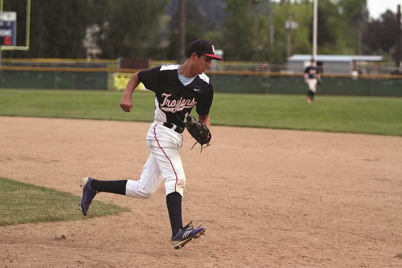 PHIL HAWKINS - Kennedy senior John Valladares fields a routine grounder and trots over to first base for the out.