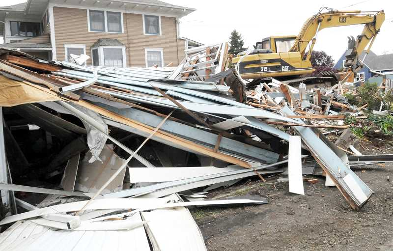 SUSAN BRANNON - Contractors made quick work of demolishing a home on School Street last week adjacent to the Newberg Public Library. The space will become a city parking lot.