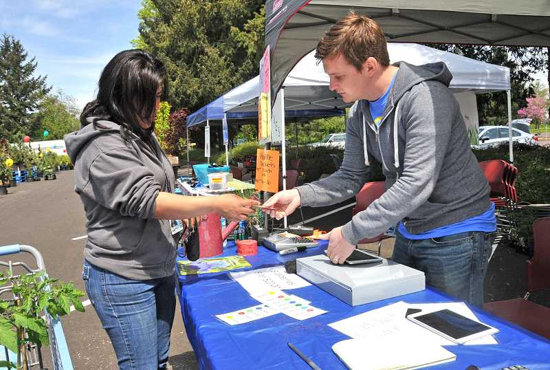 Travis Brooks helps a customer with a purchase at the Rite Aid Distribution Center Plant Sale May 5