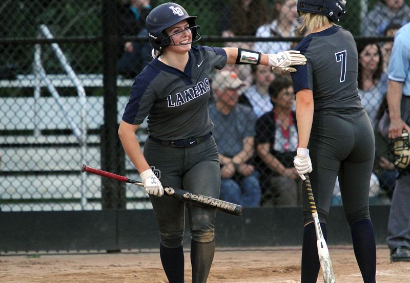 REVIEW PHOTO: MILES VANCE - Lake Oswego's Marin Penney is all smiles after she scored in the seventh inning of her team's 7-3 win over Lakeridge at Lakeridge High School on Monday.
