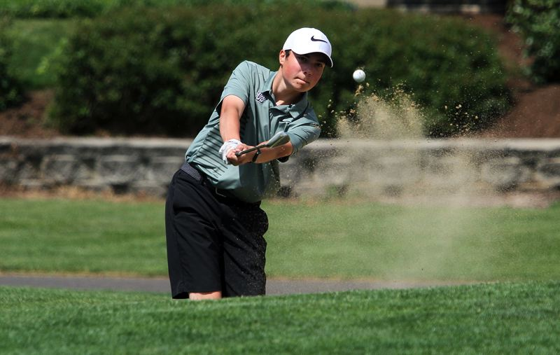 TIDINGS PHOTO: MILES VANCE - West Linn's junior Sebastian Hardin blasts out of a greenside bunker during the 6A Special District 2 regional tournament at the OGA Golf Course at Tukwila on Tuesday.