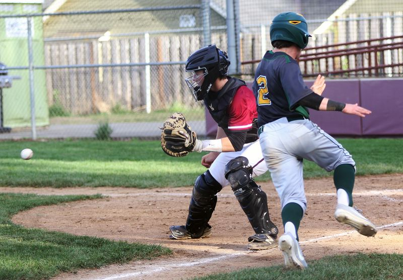 TIMES PHOTO: DAN BROOD - Sherwood senior catcher Hayden Gilbert (left) grabs for the ball as West Linn senior James Marshall crosses home plate during Tuesdays game.