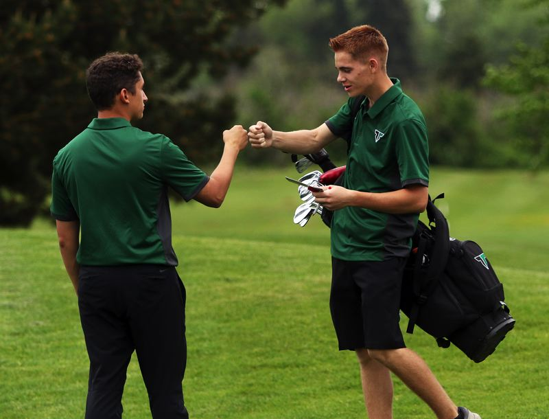 TIMES PHOTO: DAN BROOD - Tigard High School senior Abel Rodriguez (left) congratulates junior Kai Alexander after he finished play at the Special District 2 regional tournament.