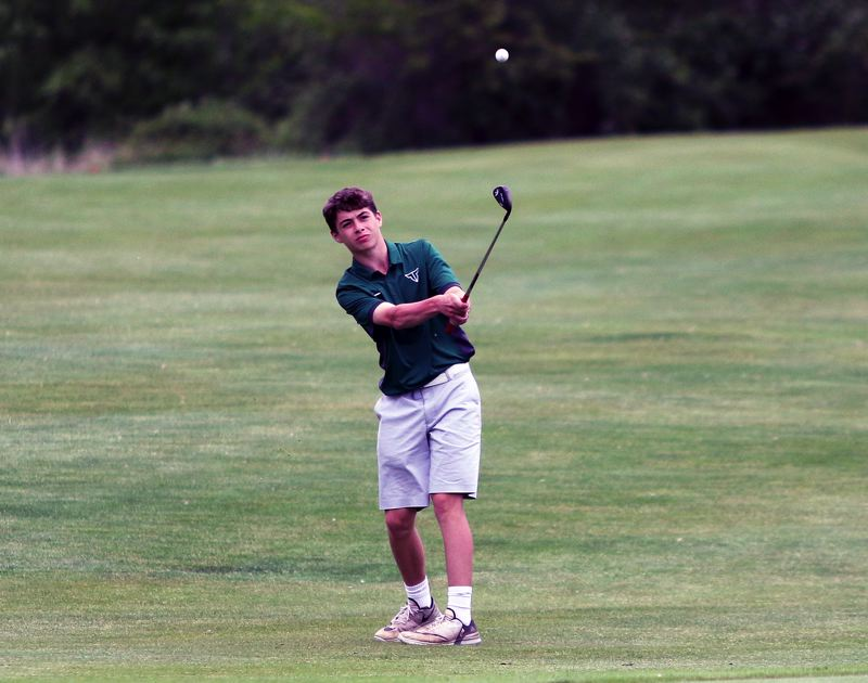 TIMES PHOTO: DAN BROOD - Tigard sophomore Graham Oelke chips onto the green during play Tuesday at the Special District 2 regional tournament.