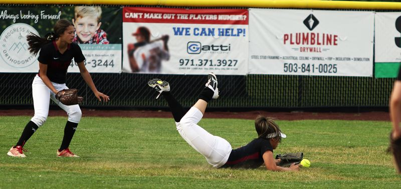 TIMES PHOTO: DAN BROOD - Tualatin High School senior center fielder Zoe Olivera, with sophomore Tia Ridings behind her, makes a diving attempt to catch a fly ball during the game at Tigard.