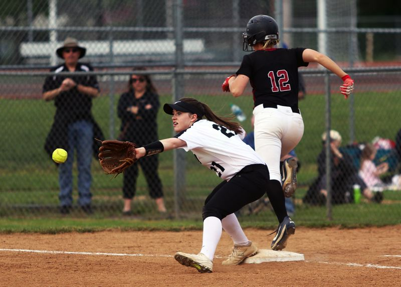 TIMES PHOTO: DAN BROOD - Tualatin senior Ella Hillier (12) is safe at first base as Tigard senior Caroline Riggs reaches for the ball during the teams game on Friday.