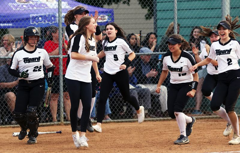 TIMES PHOTO: DAN BROOD - Tigard High School players race to the plate following sophomore Lexi Klums three-run home run in the seventh inning of Fridays game.