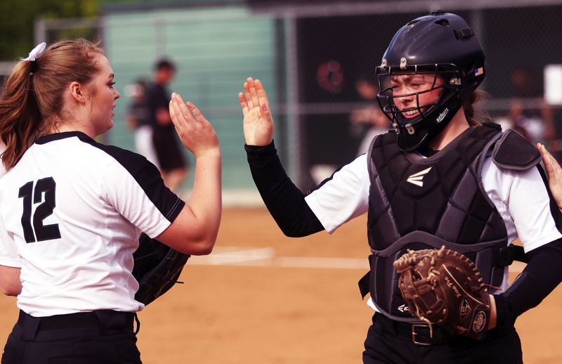 TIMES PHOTO: DAN BROOD - Tigard senior Ashley Davis (left) and sophomore Emily Paulson share a high five between innings.