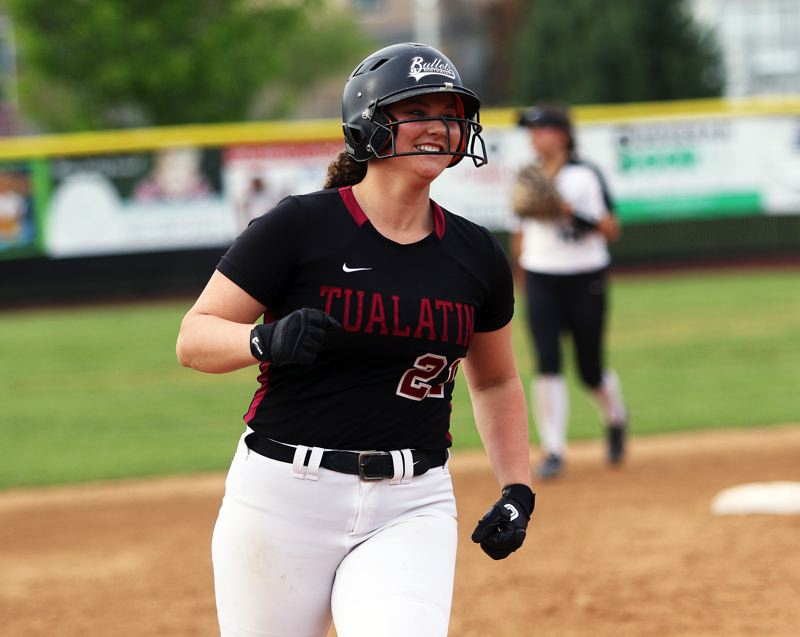 TIMES PHOTO: DAN BROOD - Tualatin junior Emily Johansen smiles as she rounds the bases following the first of her two home runs against Tigard.