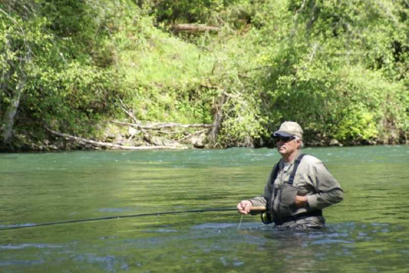 COURTESY PHOTO: CLACKAMAS FLY FISHERS - CFF President Gil Henderson sits waste deep waiting for a bite on the end of his line.