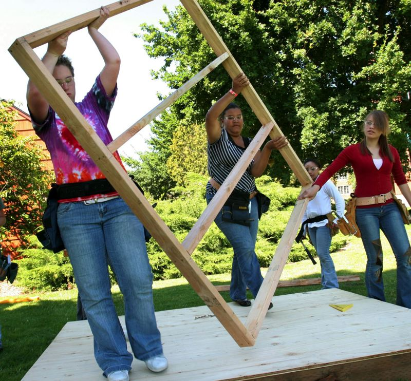 PAMPLIN MEDIA GROUP: FILE PHOTO - Girls attending Oregon Tradeswomen, Inc.'s past Building Girls High School Week at the University of Portland carry one of the walls they assembled for a playhouse.