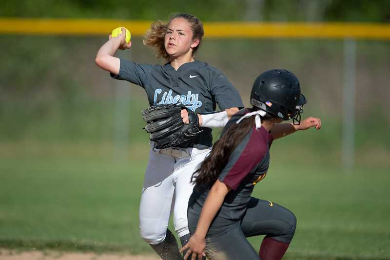 STAFF PHOTO: CHRISTOPHER OERTELL - Liberty's Katelyn Bickford sets to throw to first during the Falcons' game against Forest Grove Tuesday, May 8, at Liberty High School.