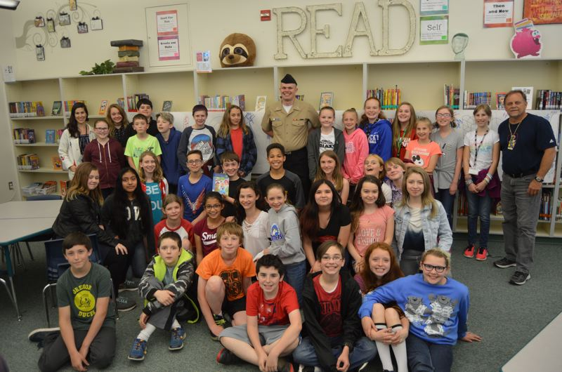 SPOTLIGHT PHOTO: NICOLE THILL-PACHECO - Students pose for a group photo with Eisen White, center, after visiting with him at Columbia City Elementary School on May 4. Behind the group is a thank-you poster the students made for White.