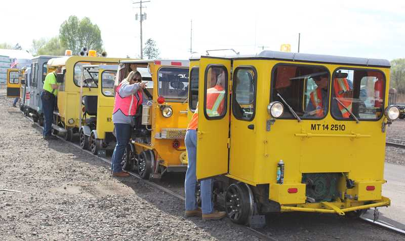 JASON CHANEY - Speeder car owners prep their vehicles, which were once used by railways across the country to transport employees, for a trip down the City of Prineville Railway. The group came from multiple states to visit the local track.