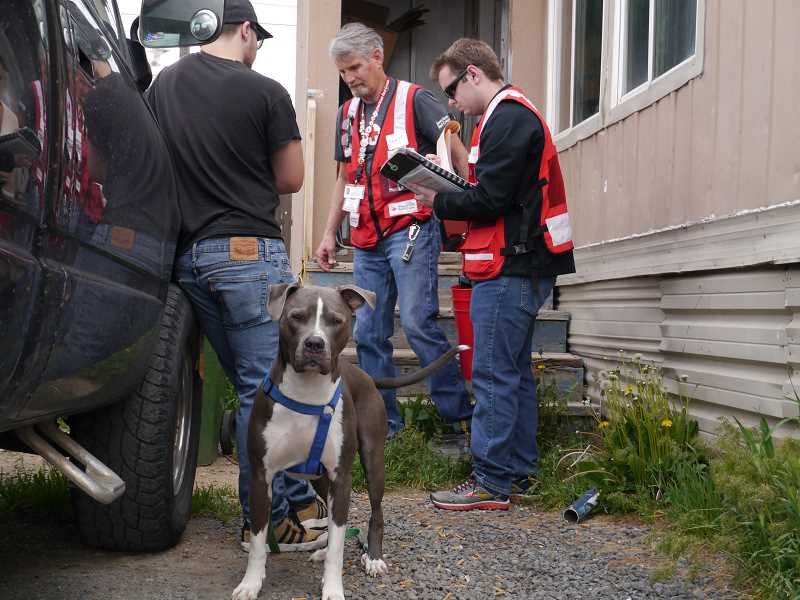SUBMITTED PHOTO - From left, Madras resident Quaid Fuller, with his dog, visits with Red Cross volunteers Jack Crowell and Levi Miller, who were preparing to install free smoke detectors in Fuller's residence on Saturday.
