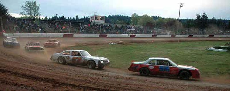 SPOTLIGHT PHOTO: MIKE WEBER - Terry King of Warren (right) drives his 1987 Buick Regal while leading the Street Stock main, with defending series champion Greg Brumbaugh of St. Helens following closely behind in his 1985Chevrolet Malibu.