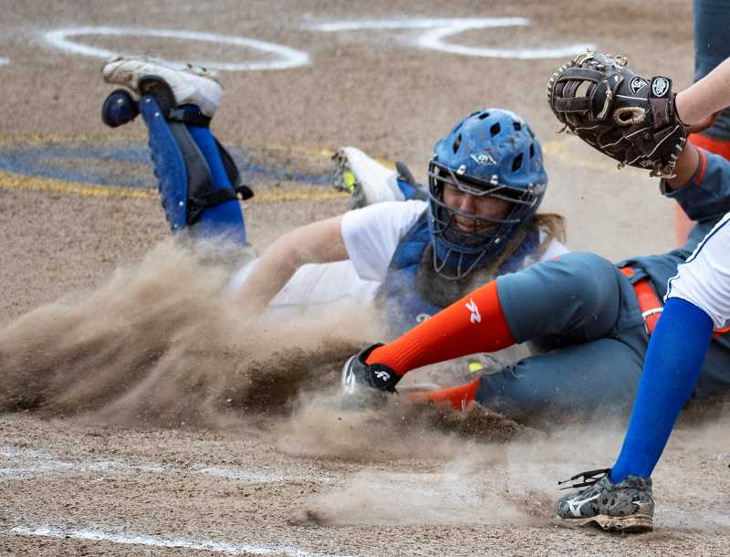 LON AUSTIN/CENTRAL OREGONIAN - Caitlyn Elliott makes a diving tag of Gladstone's Dessie Alvarado, saving a run. Elliott's play came when Alvarado tried to score following a wild pitch.