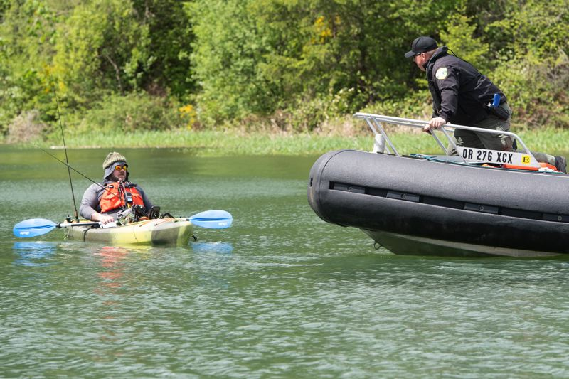 STAFF PHOTO: CHRISTOPHER OERTELL - Washington County Sgt. Rich Musser role-plays as a fisherman in a kayak, providing a scenario for students learning how to make contact with different types of boaters, during training exercises for new marine patrol officers on Henry Hagg Lake.