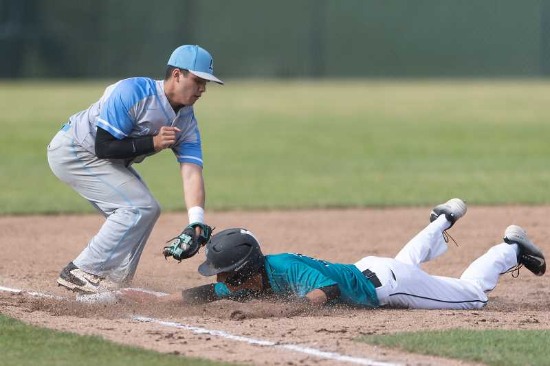 STAFF PHOTO: CHRISTOPHER OERTELL - Century's Blake Baccay slides in under the tag of Liberty's Xaven Unciano during the Jaguars' game against the Falcons Thursday, May 10, at Century High School.