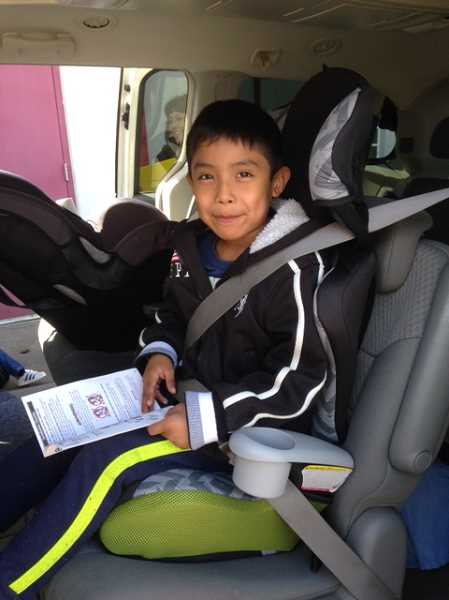 COURTESY PHOTO - At the event, professionals helped families learn to safely strap their kids into their cars.