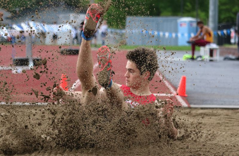 PAMPLIN MEDIA PHOTO: JIM BESEDA - Oregon City's Jake Follett lands a jump of 22 feet, 7 inches to win the boys' long jump title at Wednesday's Mt. Hood Conference track and field championships at Gresham High School.