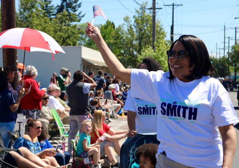 TRIBUNE PHOTO: ZANE SPARLING - Multnomah County Commissioner Loretta Smith waves a flag during the St. Johns Parade on Saturday, May 12 in Portland.